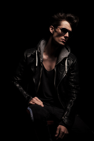 male hair: side view of dramatic young man in leather jacket posing in studio Stock Photo