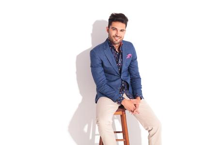 uomo felice: uomo sorridente rilassato in vestito che si siede su uno sgabello e guarda la telecamera in studio