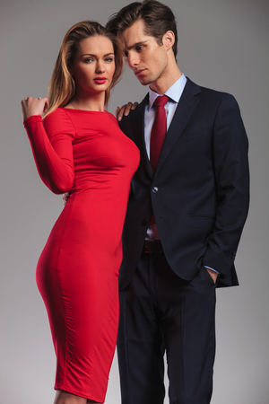 dress suit: young elegant couple standing embraced, man in suit and tie, woman in red dress