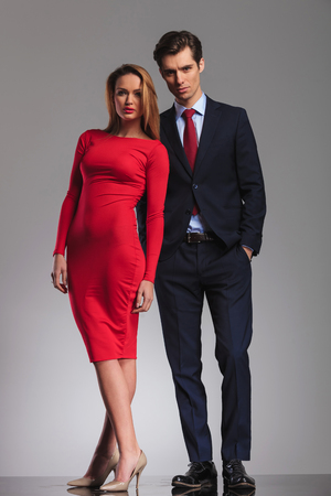 hand in pocket: Sexy blonde woman red dress standing next to Young businessman with hands in pockets in studio