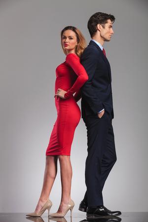 joven pareja elegante de pie espalda con espalda en el estudio, mujer de vestido rojo, hombre de traje Foto de archivo