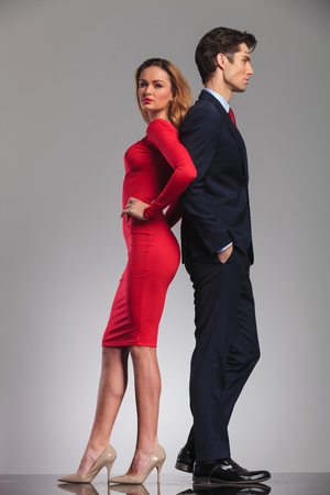 full suit: young elegant couple standing back to back in studio, woman in red dress, man in suit