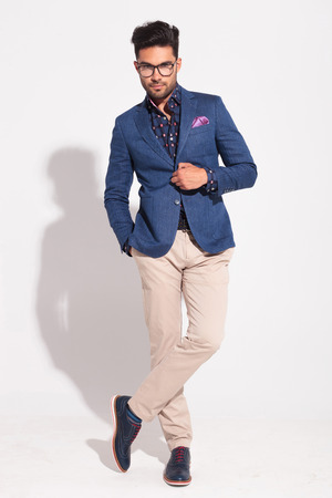 young fashion male model in suit holding button and posing in studio