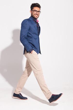 スタジオのカメラを見て幸せな歩くビジネスマンの側面図