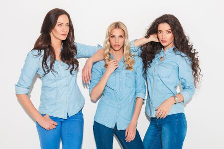 leaning on elbows: three fashion women in jeans clothes posing in studio