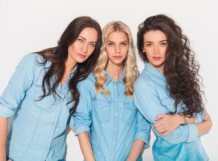 tres mujeres amigos en ropa de jeans de pie cerca uno del otro y mirar a la cámara en el estudio