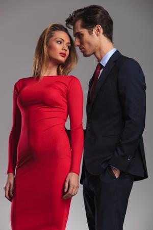 giovane coppia sexy pronto a baciare, uomo elegante in tuta in piedi nella parte posteriore di una bella donna in abito rosso