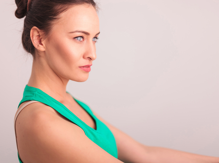 undershirt: side view of a beautiful woman in green undershirt looking away from the camera