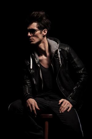 hombre sentado: vista lateral del hombre joven dramática en la chaqueta de cuero que mira lejos de la cámara en el estudio
