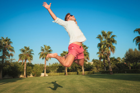 ecstatic young casual man jumping of joy in an exotic garden with palm trees in hte background