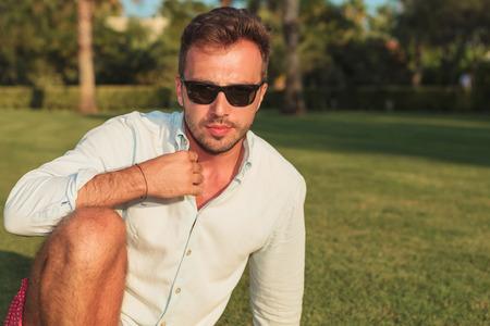 hombre sentado: hombre sentado en el aire libre que sostiene el cuello y se ve bien para la c�mara Foto de archivo