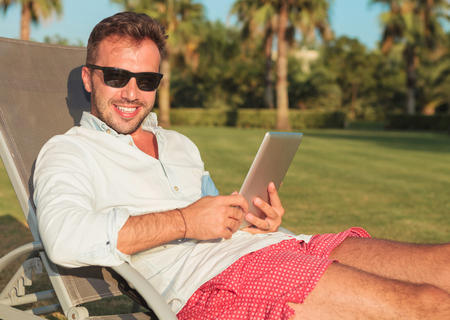 people relaxing: side view of a seated man in sunglasses holding a tablet pad computer and smiles for the camera