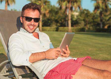 hombre sentado: vista lateral de un hombre sentado en gafas de sol que sostiene un ordenador de la pista de la tableta y sonr�e para la c�mara