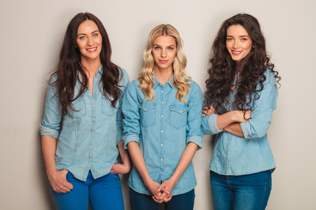 three women: group of three casual women in jeans clothes standin in studio Stock Photo