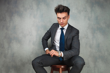 checking time: young seated business man checking time on his watch in studio Stock Photo