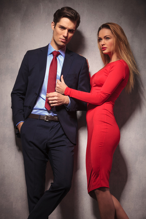 relaxed business man: relaxed business man posing while sexy young blonde woman in pulling his coat