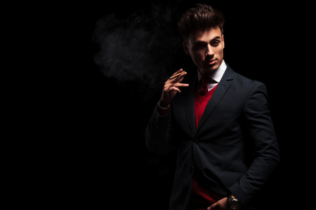 elegant young businessman standing and smoking in studio, with copy space to side