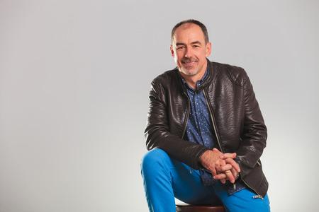 hombres maduros: sonriente hombre maduro en la chaqueta de cuero que descansa sobre una silla en estudio
