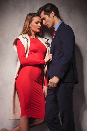 together with long tie: sexy elegant couple standing close to each other, woman pulling business mans suit in studio Stock Photo