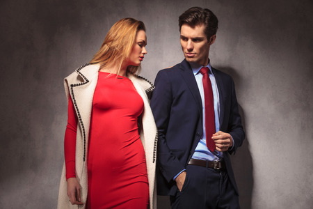 together with long tie: dramatic young elegant couple posing together in studio, woman in red dress and long coat, man in suit and tie