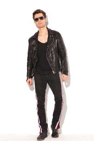 full body picture of an arrogant young fashion man in leather jacket and sunglasses posing on white background Stock Photo