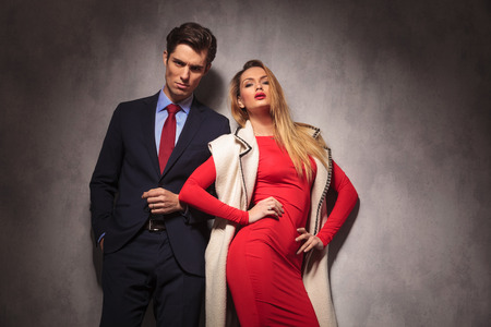 together with long tie: provocative blonde woman in red dress posing near her lover dressed in suit and tie