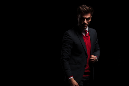 serious young business man standing on black background in studio Stock Photo