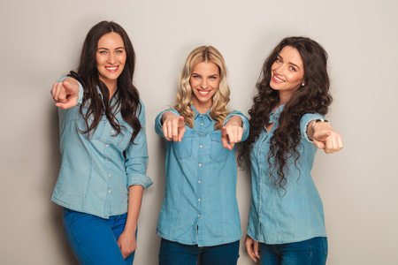 pointing fingers: three happy women in jeans clothes pointing fingers to the camera  in studio