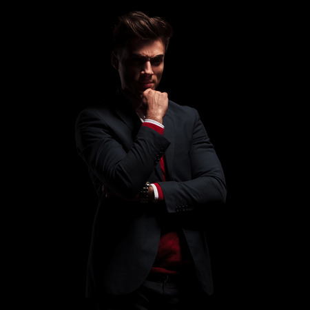 angry young businessman is thinking on black studio background