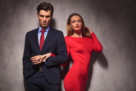 Pareja atractiva elegante de la mano, hombre de traje y corbata, mujer de vestido rojo