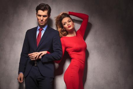 Vrouw in rode jurk die haar haar vasthoudt terwijl ze haar vriendje in pak houdt en met de hand in de studio vastlopen Stockfoto