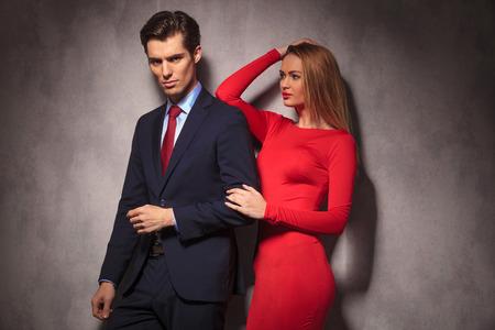 parejas amor: vista lateral de una pareja joven y elegante, mujer de vestido rojo que mira a su amante en traje y corbata Foto de archivo