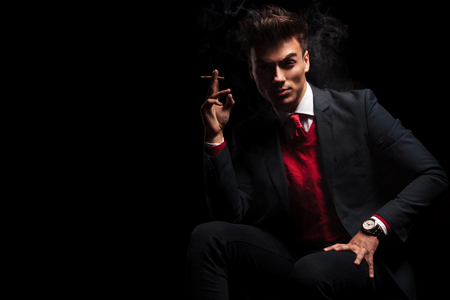 sexy elegant man in suit and tie enjoying his cigarette while sitting on black studio background