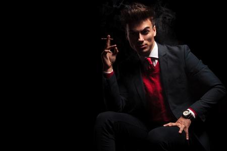 Sexy elegante man in pak en das genieten van zijn sigaret terwijl zittend op zwarte studio achtergrond