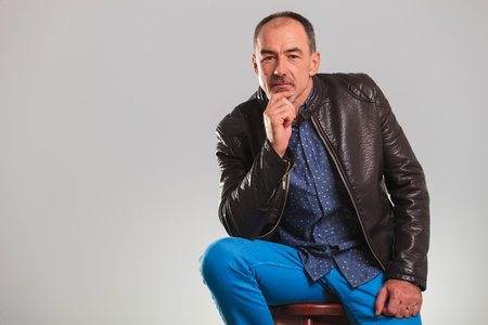 hombre sentado: hombre en la chaqueta de cuero pensando en estudio con el espacio de la copia Foto de archivo