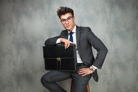 relaxed business man: relaxed business man holding a suitcase is sitting on a chair in studio