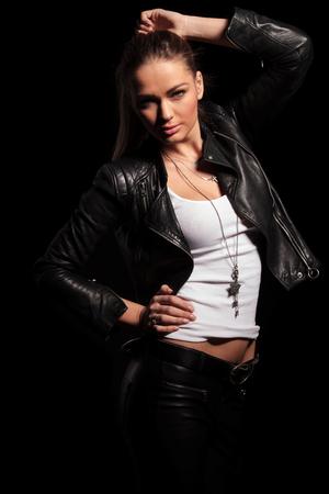 jacket: Mujer rubia atractiva en ropa de cuero posa para la cámara en el fondo negro del estudio Foto de archivo