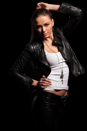 jewlery: sexy blonde woman in leather clothes poses for the camera on black studio background