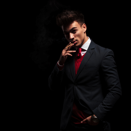 arrogant: arrogant elegant young man smoking his cigarette on black background