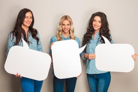 drie gelukkige vrouwen in jeans kleren tekstballonnen en lachen naar de camera in de studio