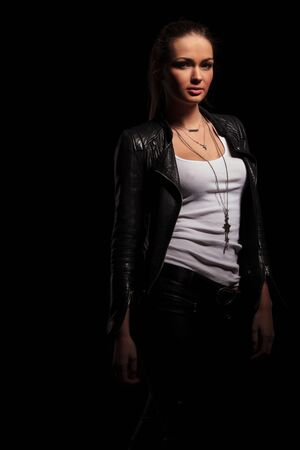undershirt: sexy woman in leather jacket and undershirt standing on black background
