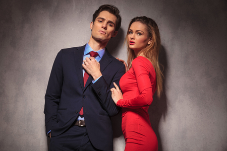 leaning on elbows: sexy business man fixing his tie while woman in red dress is leaning on his shoulder