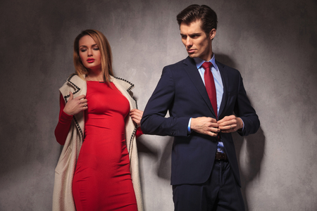 buttoning: business man buttoning his suit and looks back at his sexy blonde girlfriend wearing red dress and log coat