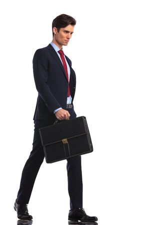 briefcase: serious and confident young business man is walking forward holding a briefcase on white background Stock Photo