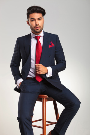 men in suit: elegant man in suit and tie sitting on a stool on grey studio background