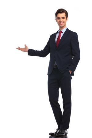 gelukkige zakenman die iets op witte achtergrond voorstelt Stockfoto