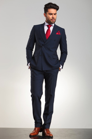 double breasted: arrogant elegant man in double breasted suit standing with hands in pockets and looks to side on grey studio background