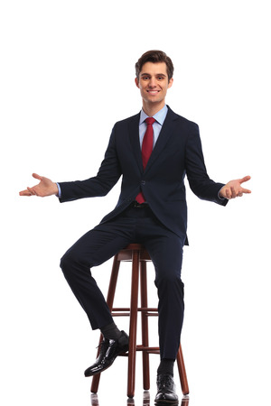 handsome young man: full body picture of a young happy business man sitting on chair and welcoming you, on white background
