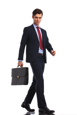stepping: attractive businessman with suitcase stepping forward on white background Stock Photo