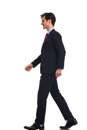 歩く若いビジネス人、白い背景で隔離の側面図
